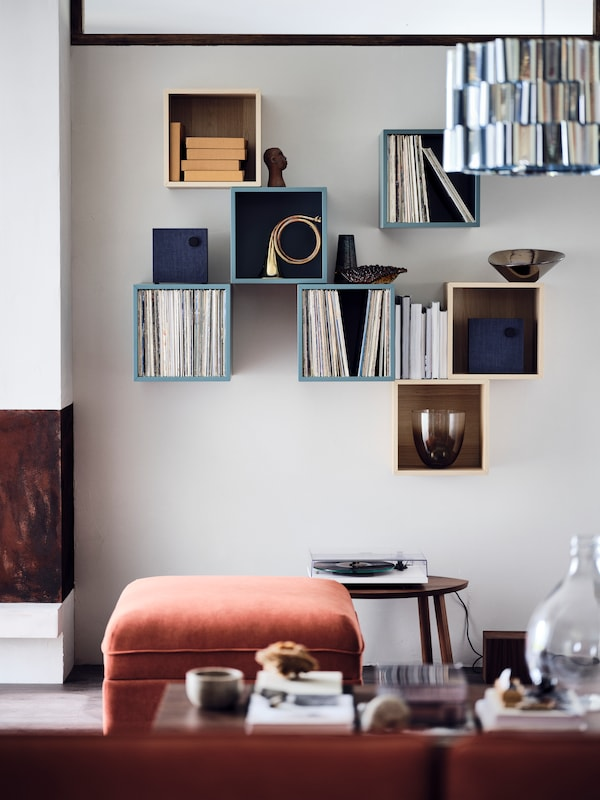 An EKET wall-mounted shelving unit filled with vinyl records and other personal objects. In the foreground a sofa in velvet material.