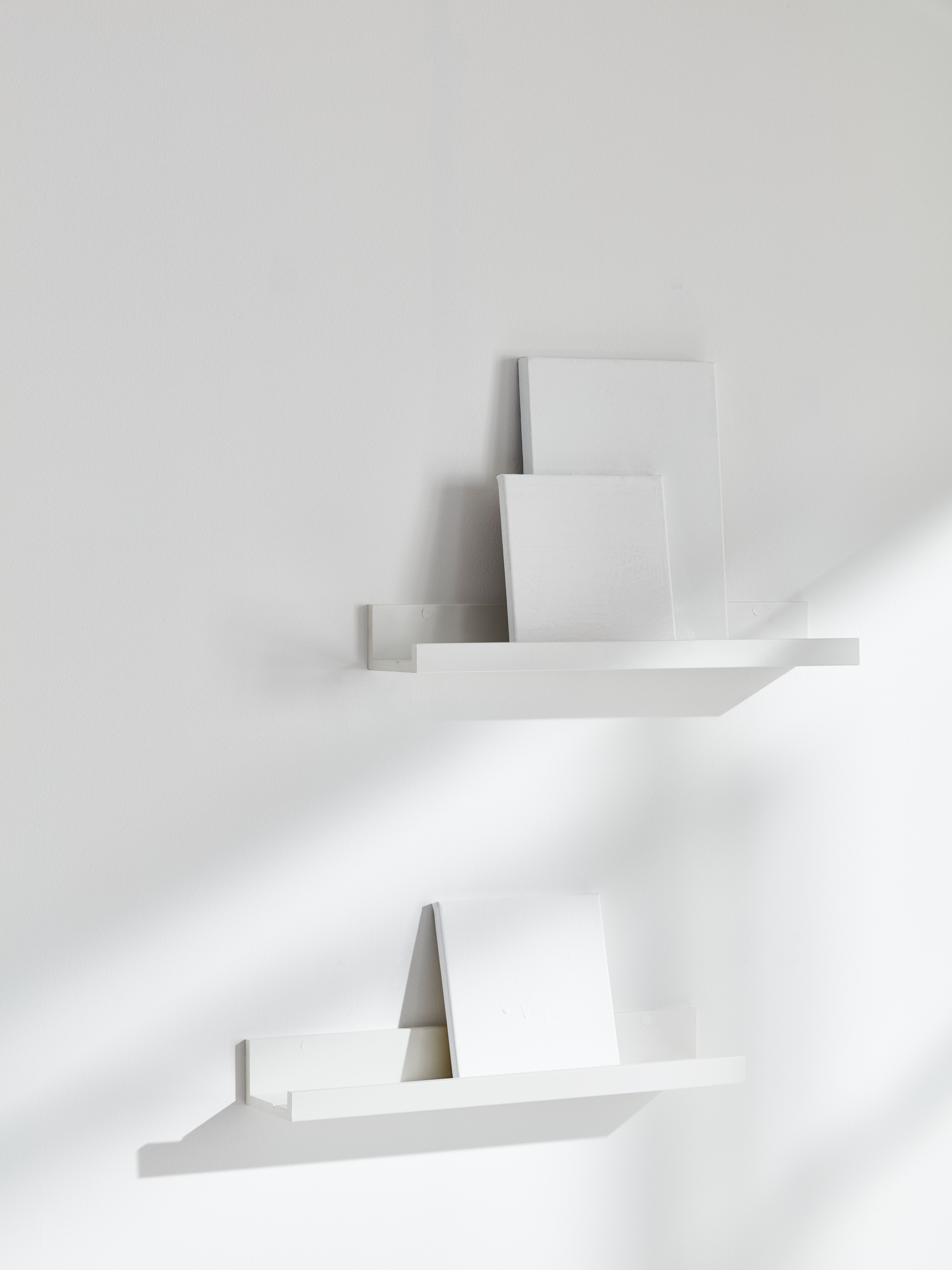 Room with white walls, two white picture ledges mounted on the wall holding blank white canvases.