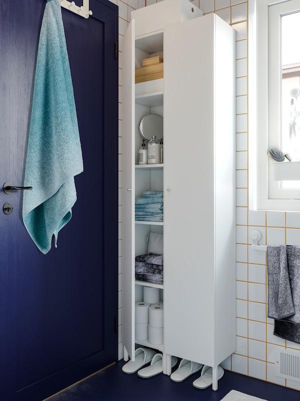 Dua kabinet tinggi berwarna putih di penjuru, di sebelah pintu berwarna biru, dengan tuala yang dilipat, kertas tisu tandas dan kelengkapan tandas di dalamnya.