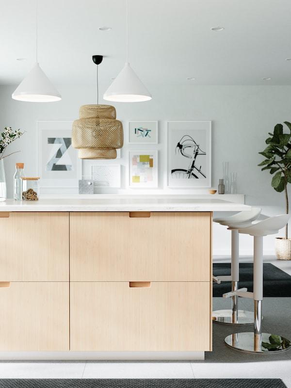Køkkenø med en bordplade med marmormønster og skuffefronter af bambus, to hvide barstole og loftlamper.