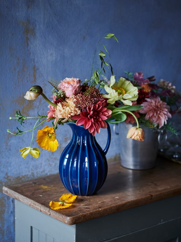 A blue jug with a bunch of flowers in many colours, in front of a metal flower holder with flowers, on a wooden surface.