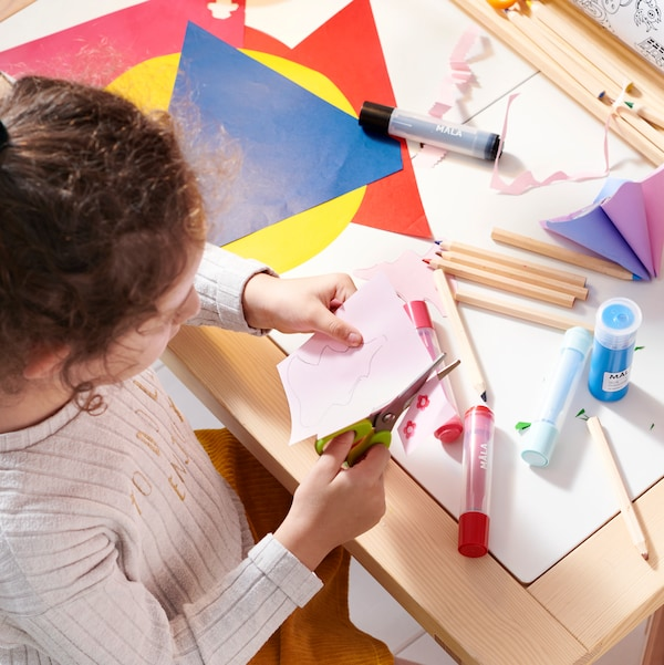A child sits at a FLISAT children's table cutting some paper. MÅLA paints and different types of paper lie on the table.