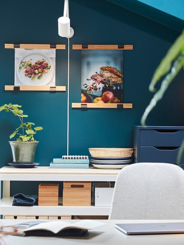 Kaksi bambusta valmistettua VISBÄCK-julisteripustinta joissa on seinälle ripustettuja ruokajulisteita, valkoinen seinävalaisin valaisee niitä kauniisti.