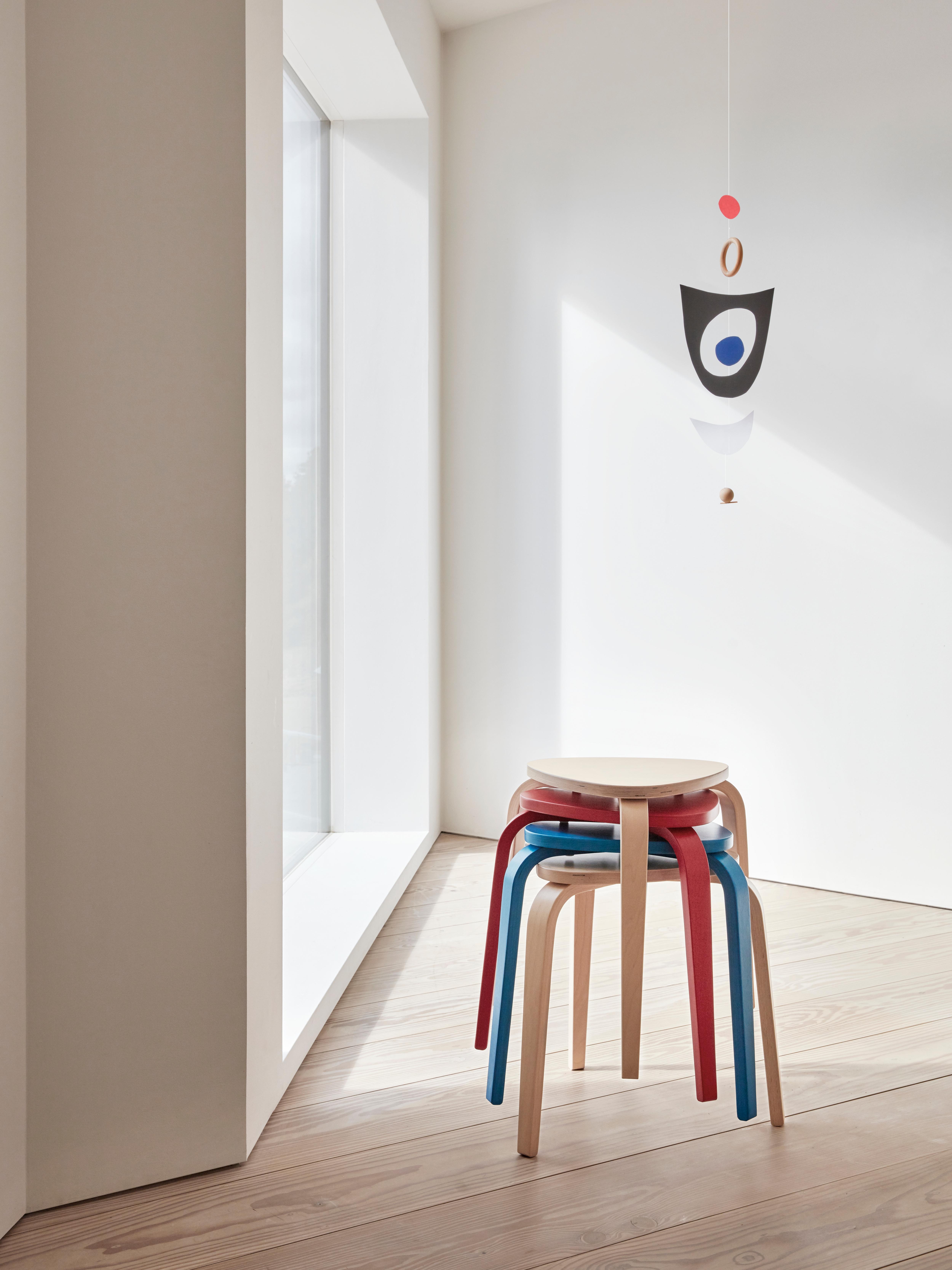 Četiri naslagana KYRRE drvena stolca od drva breze, crvene i plave boje u prostoriji s mobilom.