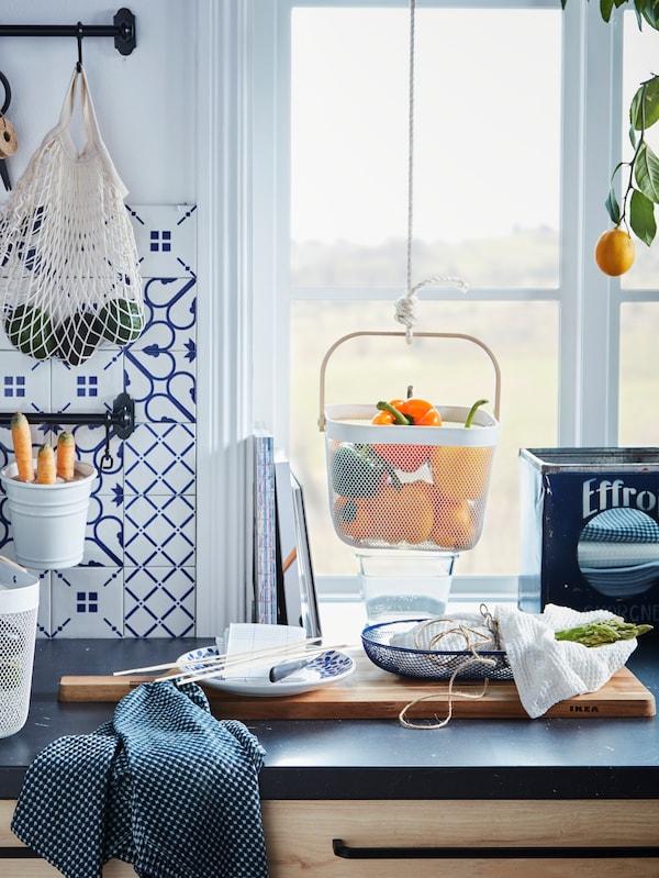 Mesado de cociña de cor escura con varios alimentos en cestas de rede de aceiro, algunhas delas penduradas, e unha bolsa de rede.