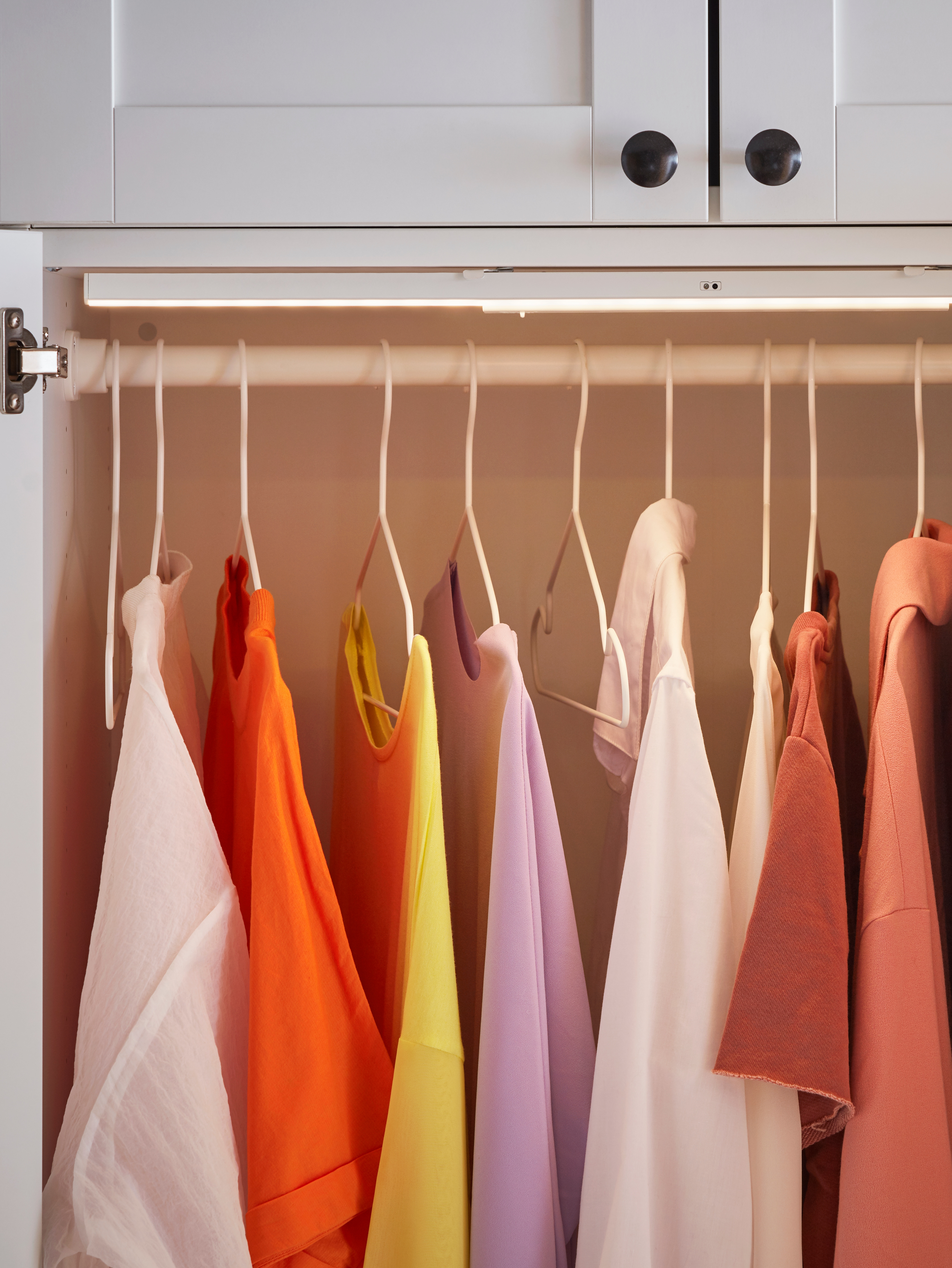 A wardrobe interior has a lighting strip above a clothes rail with colourful shirts on white, indoor/outdoor STAJLIG hangers.