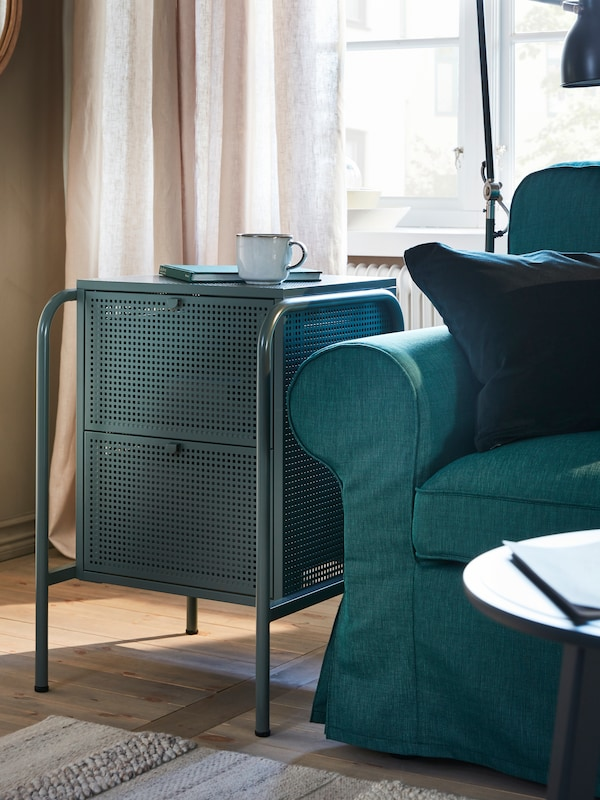 A grey-green NIKKEBY chest with 2 drawers with a GLADELIG mug and a book on it, next to a dark turquoise EKTORP sofa.