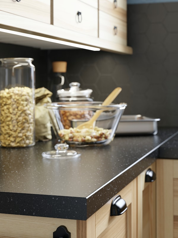 A SÄJLAN worktop with a black mineral pattern. A bowl of different kinds of nuts with a spoon in it is on the worktop.