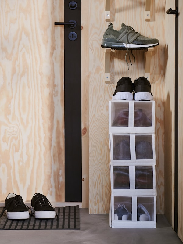 A stack of four SKUBB shoe boxes with a pair of trainers on top. Above is a pair of SANDSHULT brackets with trainers on top.