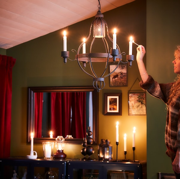 A person lighting the candles in a hanging candelabra, other candles below, a picture and a mirror on the wall behind.