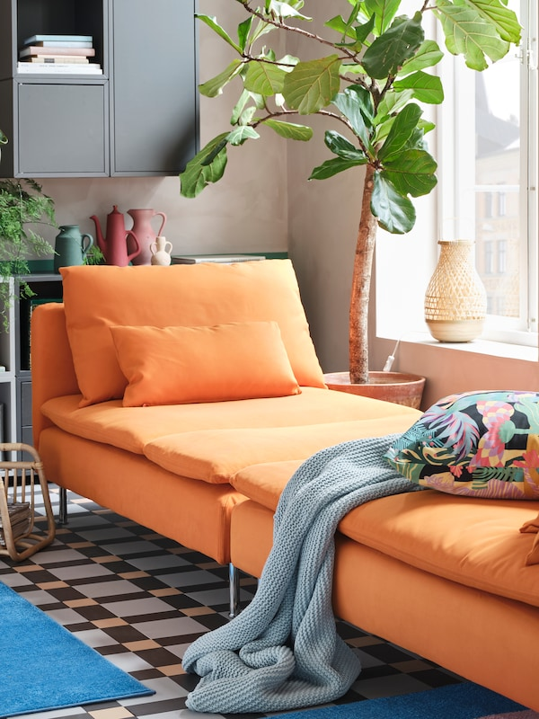 Two orange chaise lounges are standing together to create a spacious day-bed, and a blue throw and a floral cushion lie here.