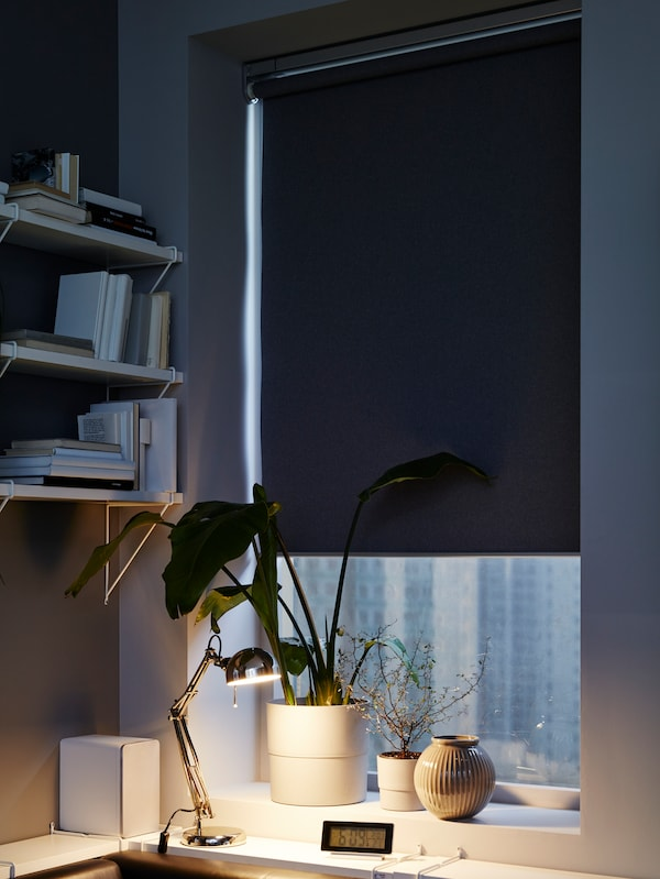 A corner in a bedroom with a FYRTUR block-out roller blind in a window near some BERGSHULT/PERSHULT wall shelves.