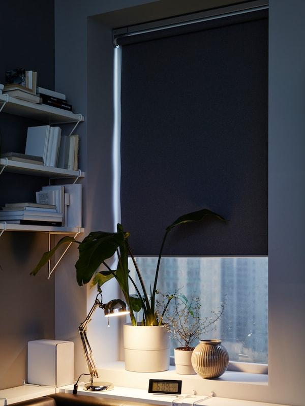 Eine Arbeitsleuchte erhellt ein paar Bücher auf einem Schreibtisch. Dahinter sind die Rückseite eines Sofas und Gardinen vor einem Fenster zu sehen.