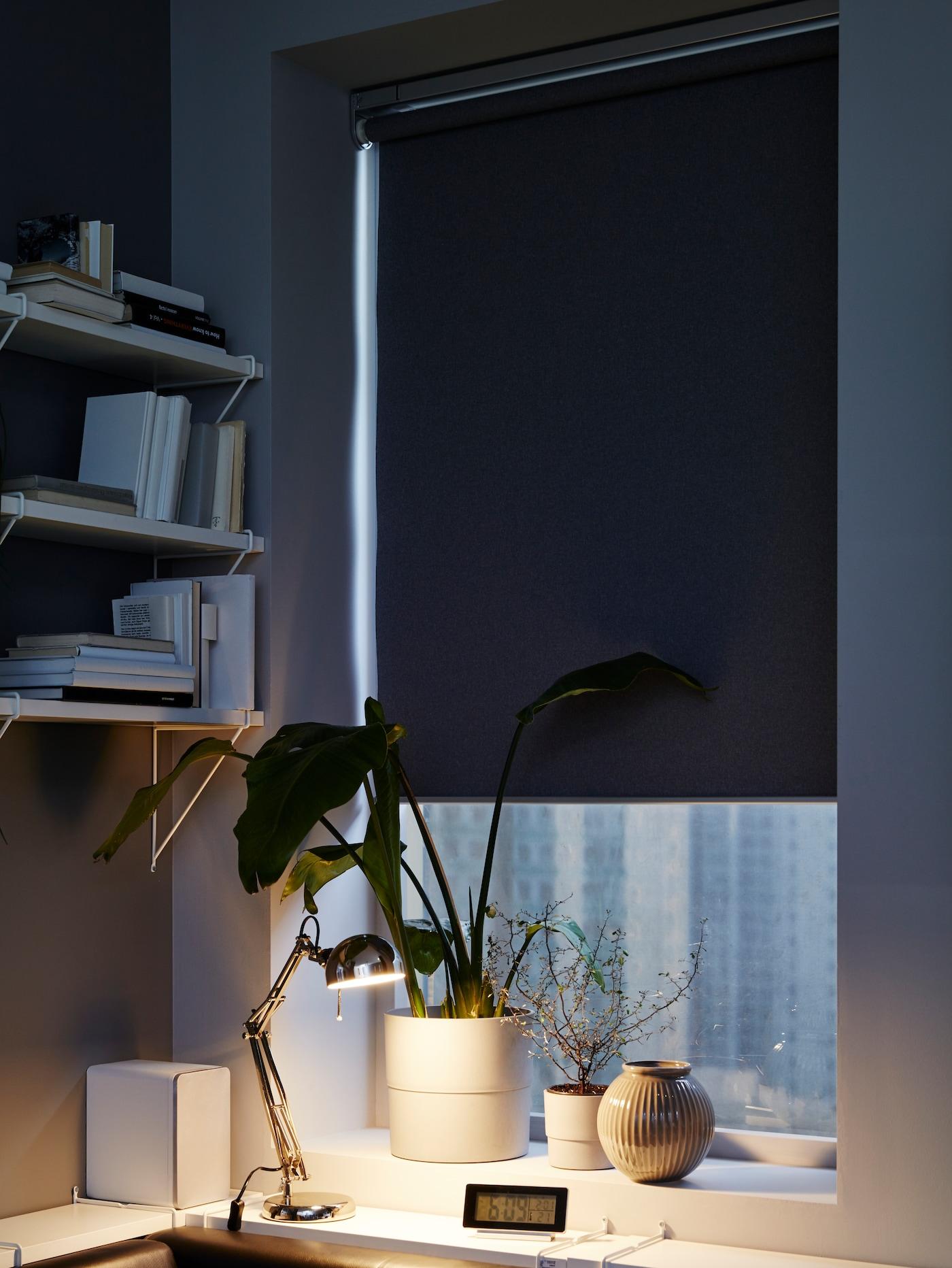 Рабочая лампа освещает книги на столе, на заднем плане видны диван и окно с гардинами.
