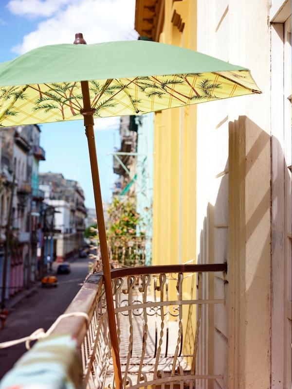 Parasol estampado en verde y amarillo, apoyado en la barandilla de un balcón con vistas a una calle.