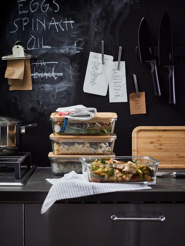 Recipientes para alimentos de vidrio IKEA 365+ apilados en la encimera de una cocina; en la pared de detrás hay una pizarra magnética.