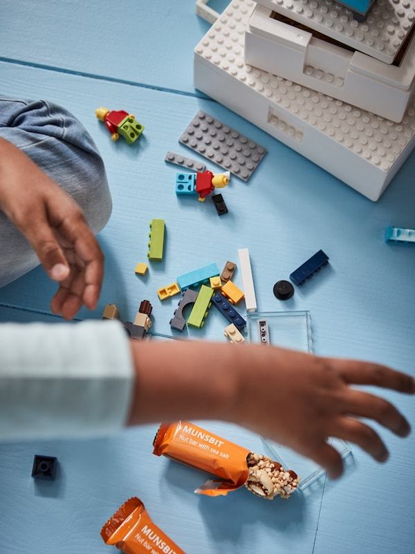 A child playing on the floor, building blocks in different colours and two MUNSBIT nut bars, one of them half-eaten.