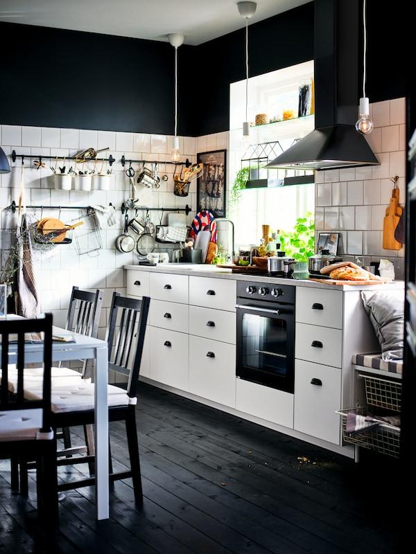 Eine schwarzweiße Küche mit weißen METOD Schränken, MAXIMERA Inneneinrichtungen, einer schwarzen Dunstabzugshaube und einem dunklen Holzboden.