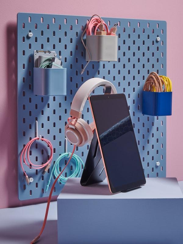 Экспозиция в розово-голубых тонах с подиумом и перфорированной панелью, на которых размещены контейнеры для хранения, подставка для планшета и пенал.