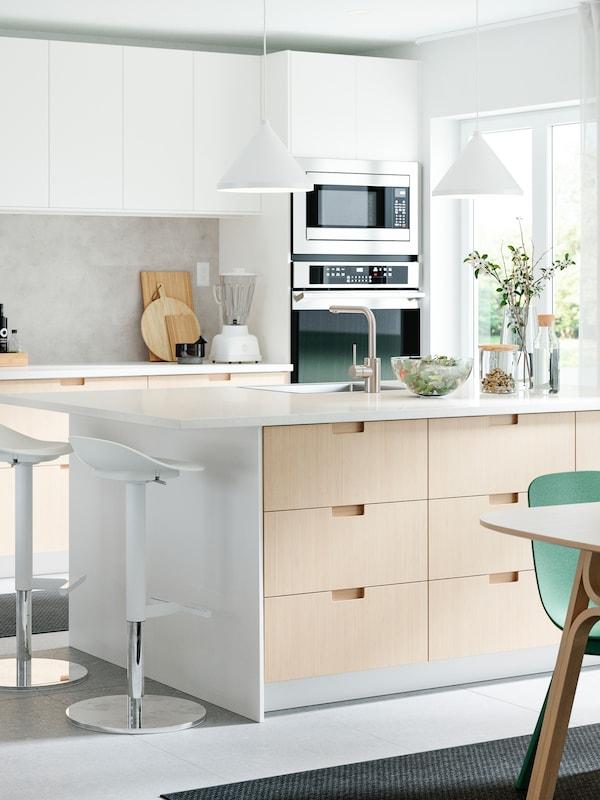 Cociña con frontes de caixón e portas brancas de bambú, unha illa, dous tallos de bar, dúas lámpadas de teito e cadeiras verdes.