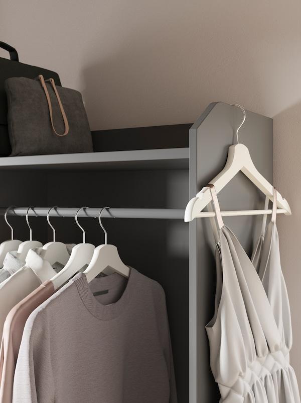 Fragment szarej otwartej szafy HAUGA z zawieszonymi na drążku ubraniami na wieszakach i jednym wieszakiem z sukienką zawieszonym na jej górnej krawędzi.