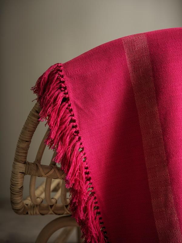 Detaily ručně tkaného texturovaného růžového plédu HILLEGÄRD přehozeného přes opěrku židle z přírodního materiálu.