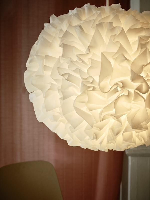 Iso, röyhelöpallon muotoinen, valkoinen lampunvarjostin, tuolin yläreuna ja vaaleanruskeat verhot takana.