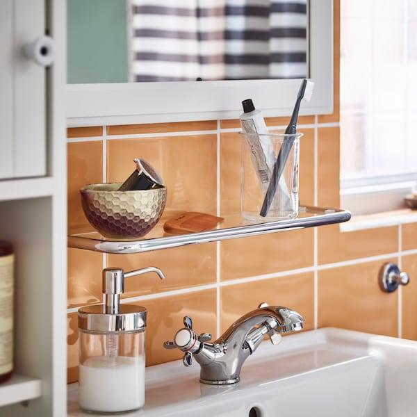 Fürdőszoba narancssárga csempével, benne mosdó RUNSKÄR csapteleppel, VOXNAN szappanadagolóval, a mosdó felett VOXNAN üvegpolc.
