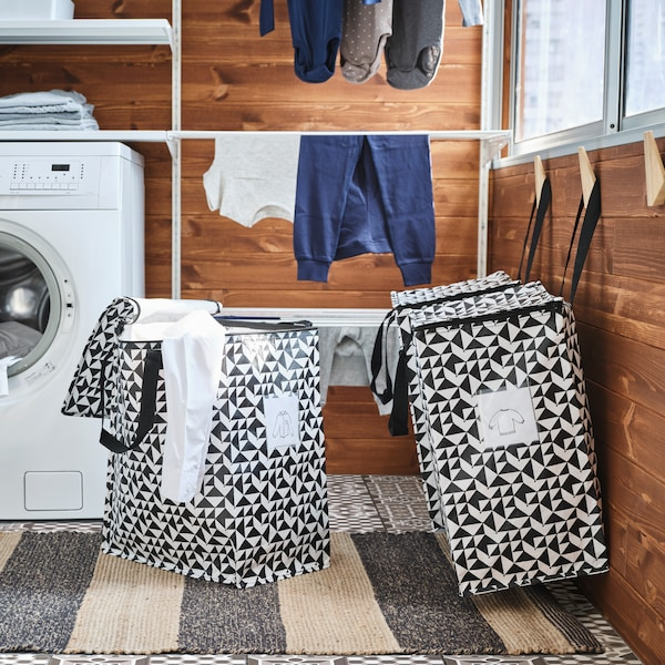 To vasketøjskurve står ved siden af en vaskemaskine og et tørrestativ i et bryggers med brune vægge.