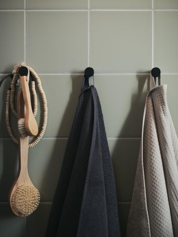 Serviettes SALVIKEN en beige foncé et anthracite sur crochets.