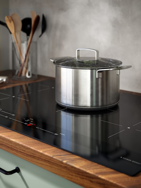A kitchen with BODARP fronts and BARKBODA kitchen worktop, a stainless steel pot is sitting on a SÄRDRAG induction hob.