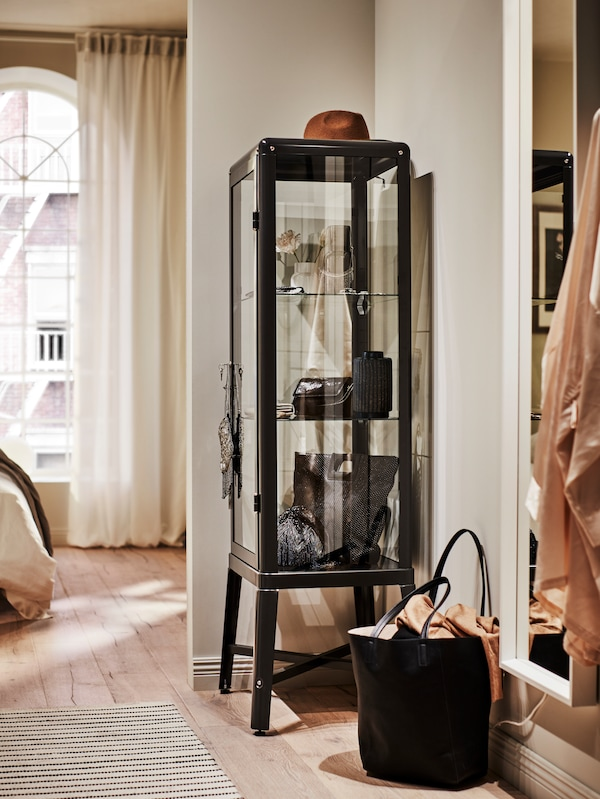 A dark grey FABRIKÖR glass-door cabinet stands in a corner, storing and displaying beautiful shoes and accessories.
