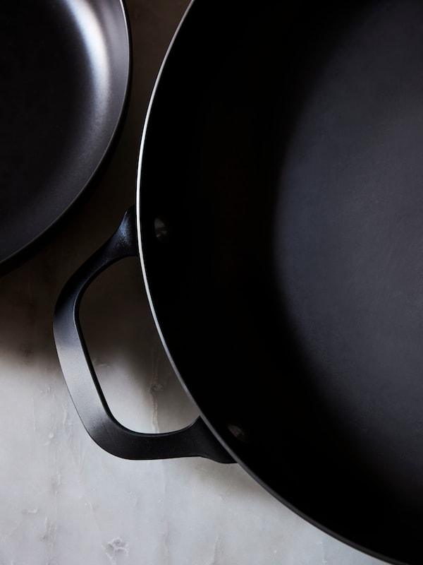 Karbono-altzairu beltzez eginiko VARDAGEN zartagin heldulekudunaren lehen planoa marmol grisezko sukalde-gainekoan jarrita.
