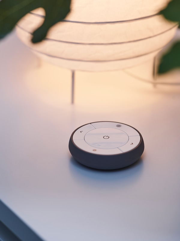 A TRÅDFRI remote control sits on a white surface near the table lamp with a rice paper lampshade that it controls.
