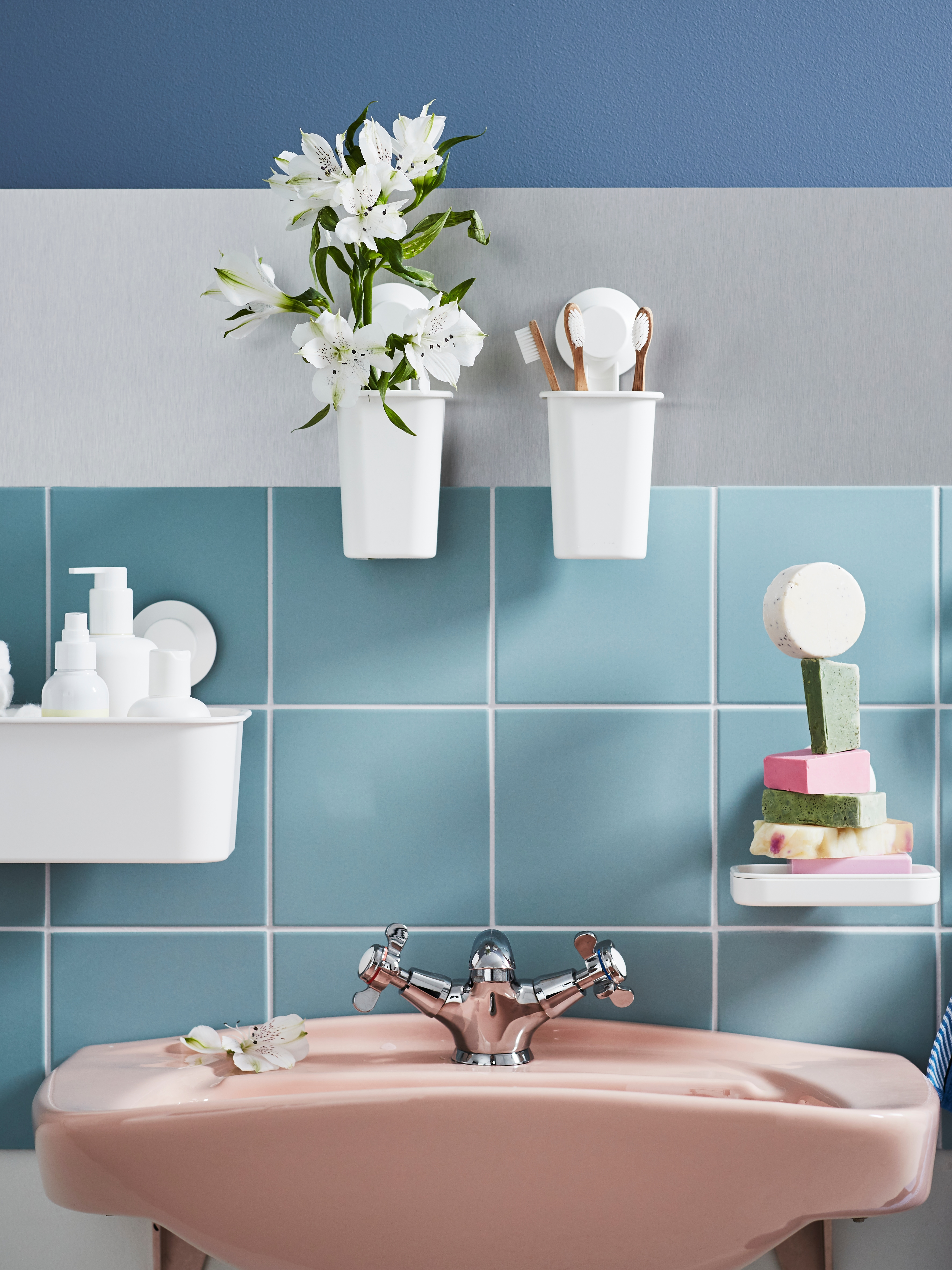 Bathroom with blue tiles, white basket, toothbrush holders and soap dish with suction cups, wash-basin, mixer tap, flowers.
