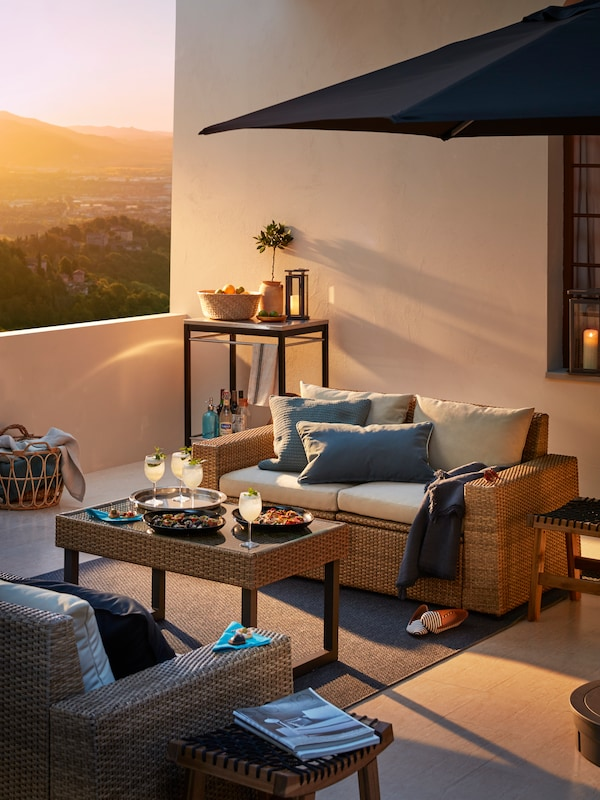 An outdoor sofa with white cushions on a terrace with an umbrella, coffee table with refreshments and an outdoor armchair.