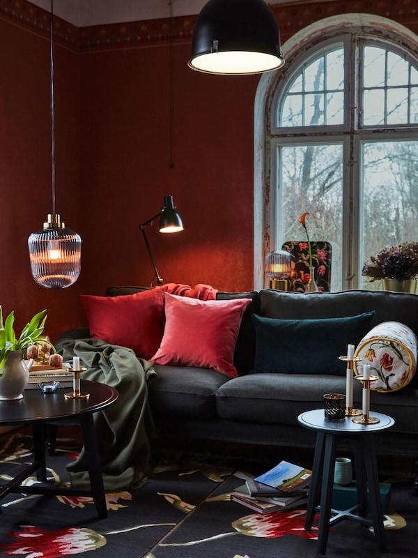 Tmavá pohovka, červené polštáře, vpředu odkládací stolek a velké okno na pozadí.