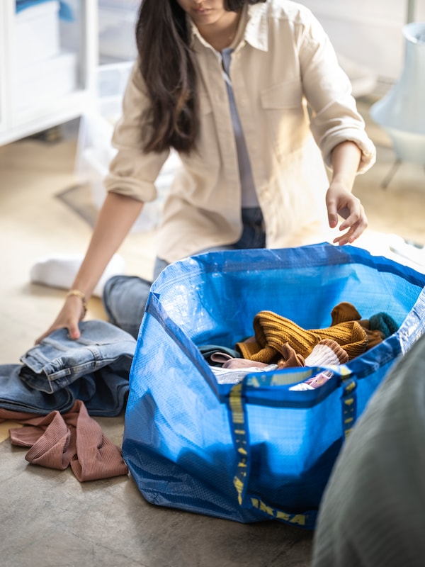 A girl sitting on the floor putting a pair of jeans into a large FRAKTA carrier bag full of clothes.
