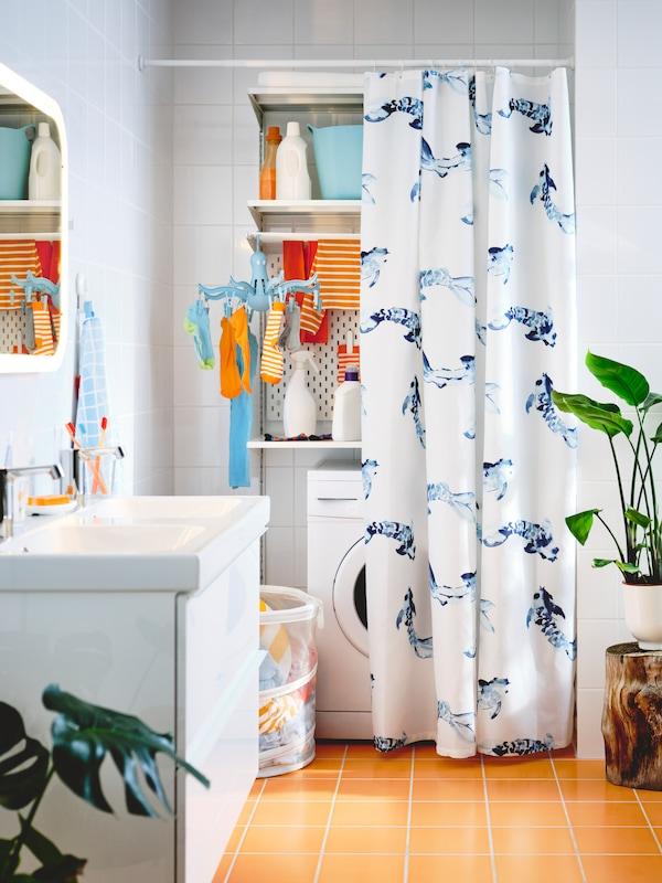 Vešernica s belim BOAXEL odeljkom s policama koji je poluskriven iza belo-plave VATTENSJÖN zavese za tuš.