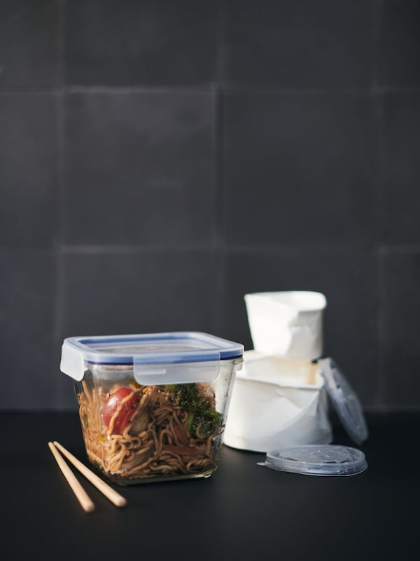 An IKEA 365+ food container holds takeaway noodles, with a discarded disposable container in the background.