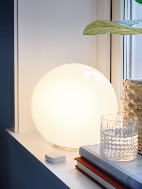 En hvid, rund bordlampe, der er tændt, et lysdæmpersæt, et glas vand og en potteplante i en vindueskarm.