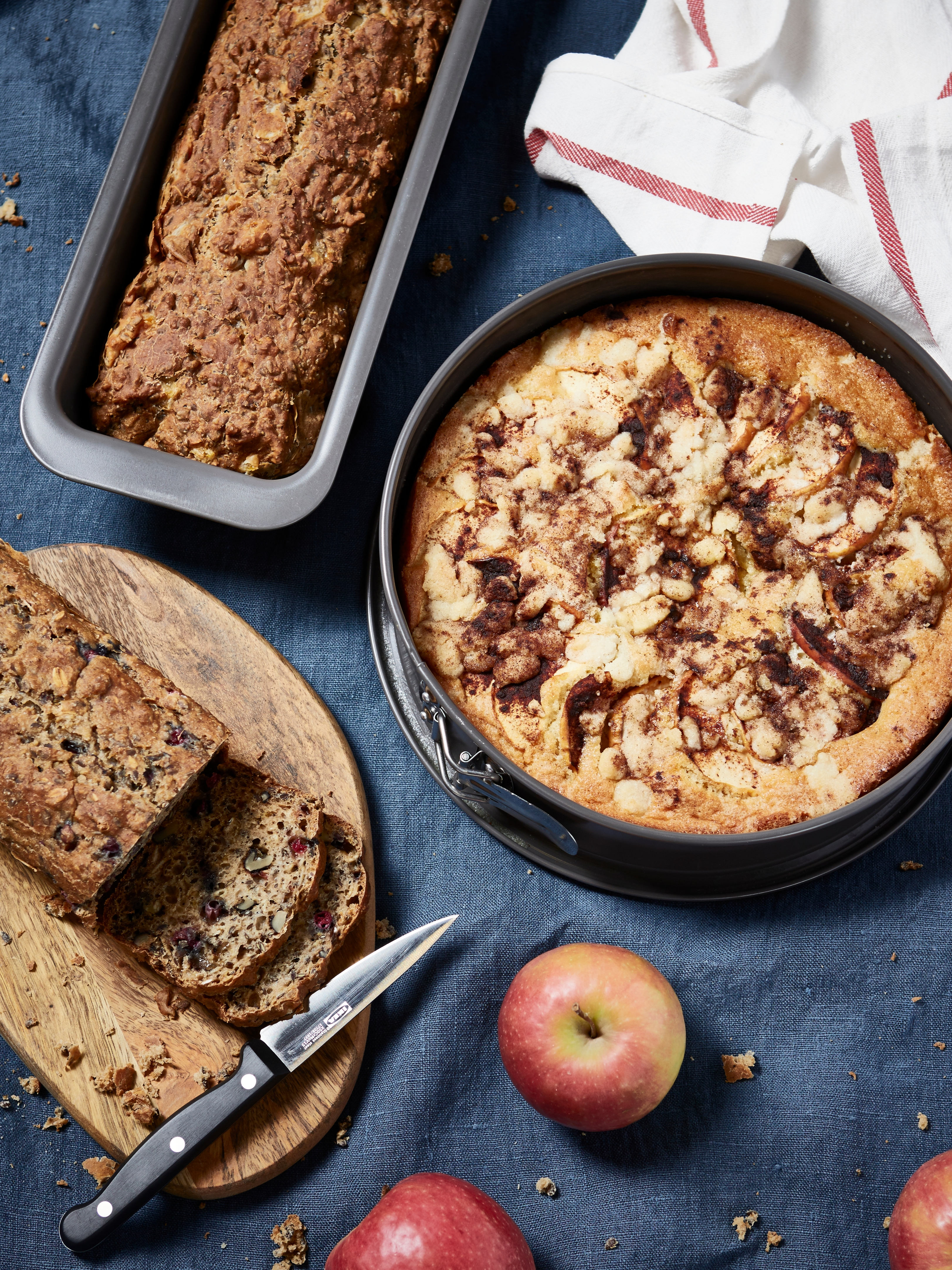 HEMMABAK springform pan with baked apple cake; cutting knife and fresh apple on the side.