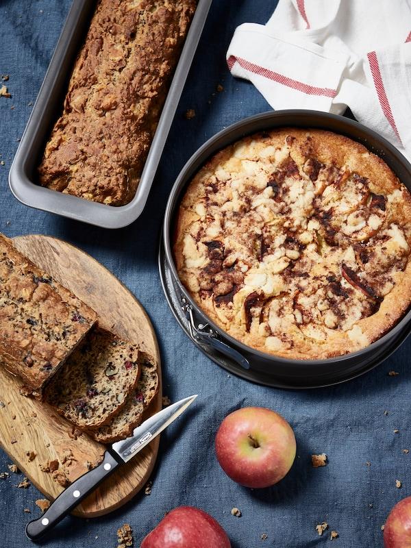 Nappe de table bleue avec une tarte aux pommes dans un plat, une miche de pain sur un plateau et une autre miche, entamée celle-là, sur une planche à découper.