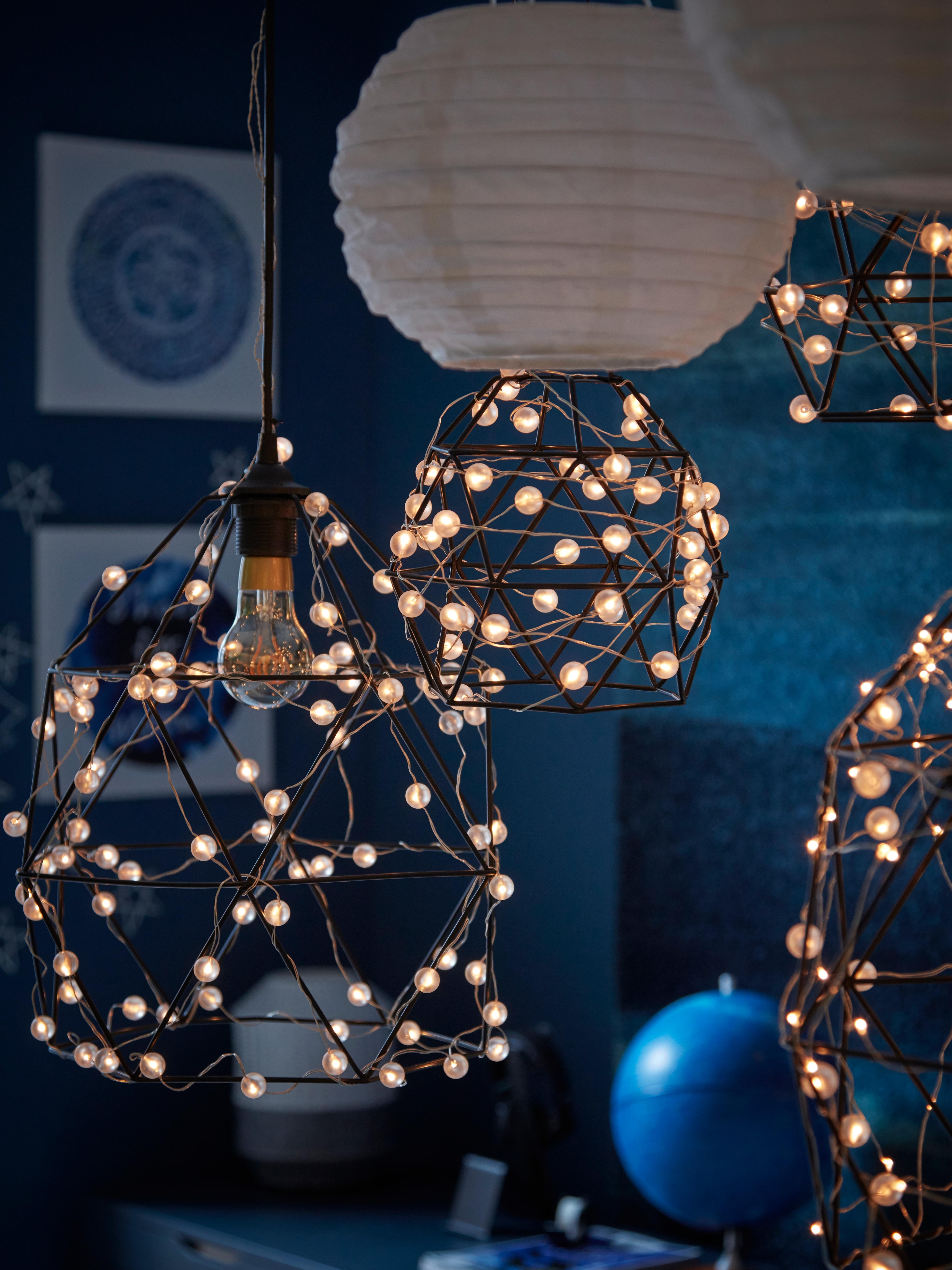 SNÖYRA LED svjetla na žici isprepletena u geometrijski oblikovanu lampu, koja visi s LED visilicama na solarno napajanje.