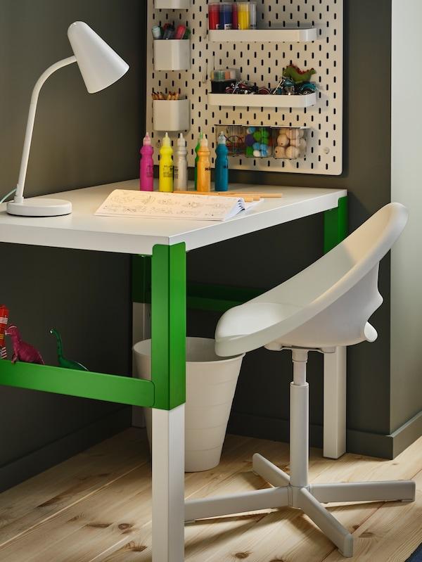 一张PÅHL 佩尔 书桌,搭配一张LOBERGET 洛贝里特/SIBBEN 西本 椅子,墙上挂着钉板。桌上有一盏灯、一本书、几种颜料和几支铅笔。