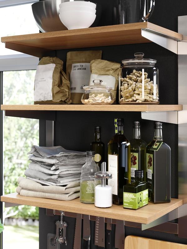 Tři otevřené dřevěné police sloužící k uložení koření, nádobí a kuchyňských utěrek.