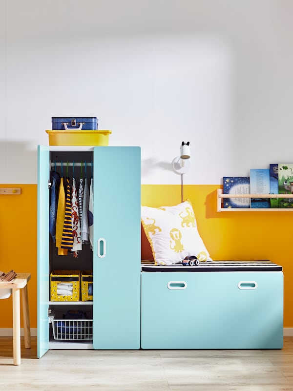 A STUVA/FRITIDS bench with toy storage and a wardrobe with light blue doors stand against a yellow and white wall.