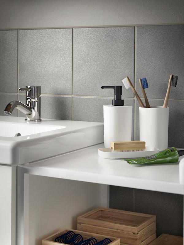 Soporte con tres cepillos de dentes, dispensador de xabón e bandexa en branco e negro nun estante a carón do lavabo.