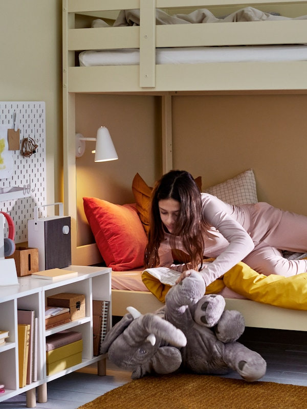 فتاة تستلقي على الطابق السفلي من سرير بطابقين به أغطية سرير بألوان متنوعة وتسحب دمية طرية JÄTTESTOR فيل من أسفل السرير.