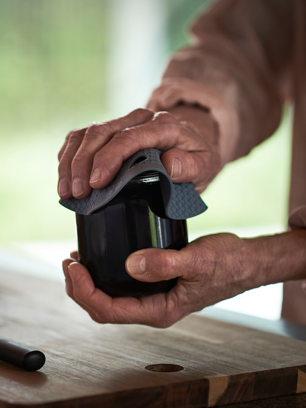 A close-up of hands using a grey OMTÄNKSAM jar gripper to open the lid of a glass jar.